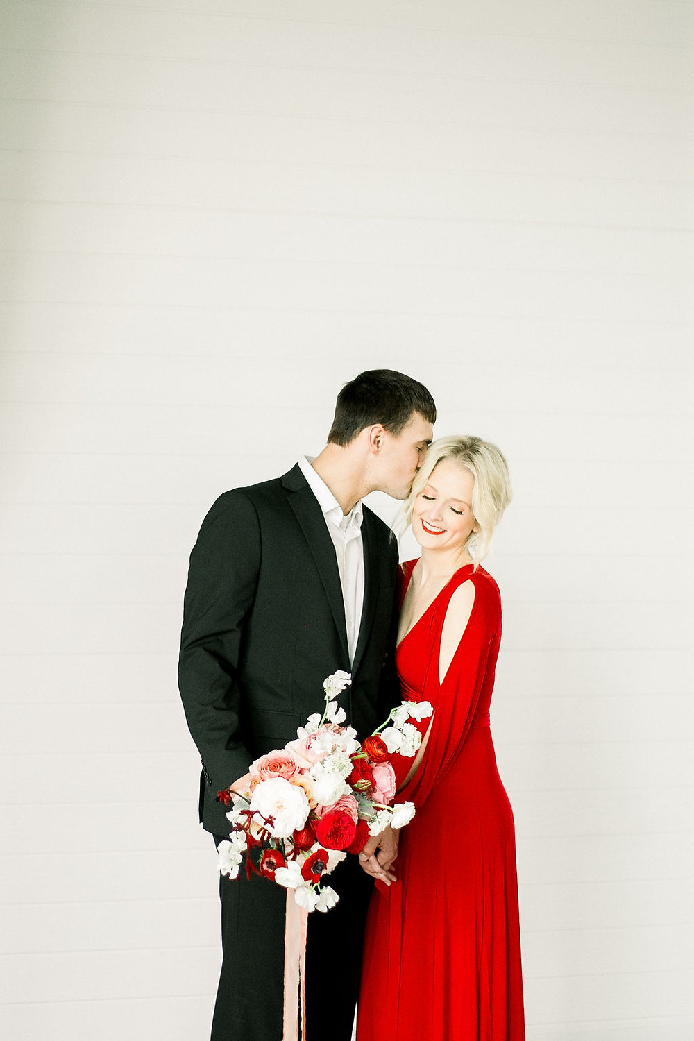 Groom kissing bride in red dress holding modern blush and red bridal bouquet by Studio Bloom Iowa against shiplap wall