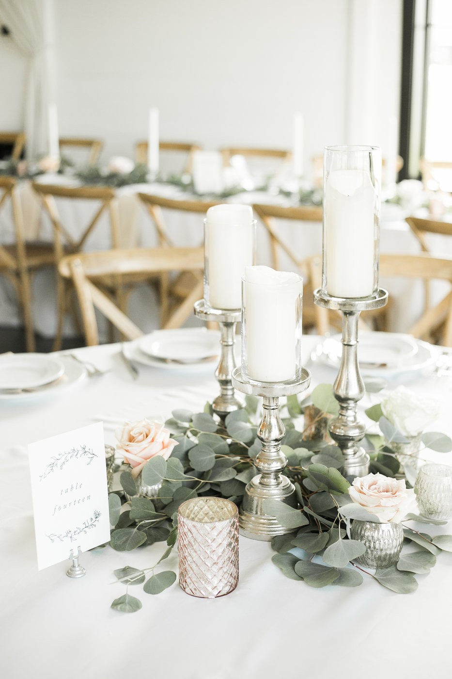 elegant greenery centerpiece with roses with silver athena candlesticks and candles by studio bloom iowa at ashton hill farm