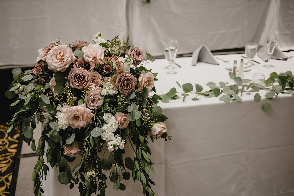 draping head table arrangement at wedding reception with mauve roses, white stock, and eucalyptus by studio bloom iowa
