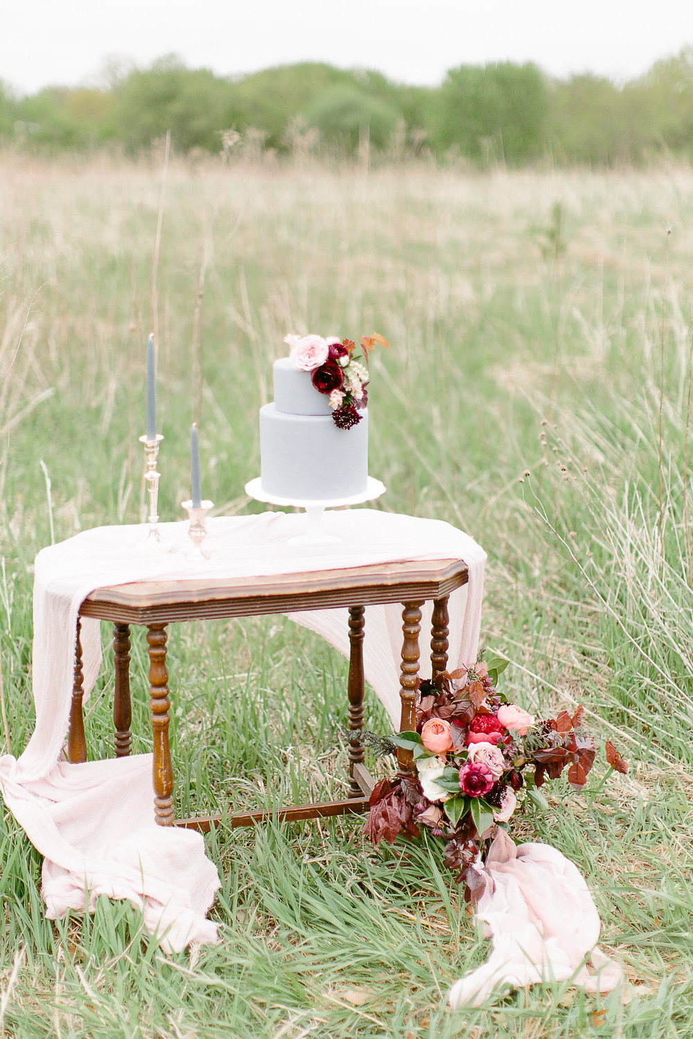 table sitting in grass field with grey fondant wedding cake and burgundy flowers