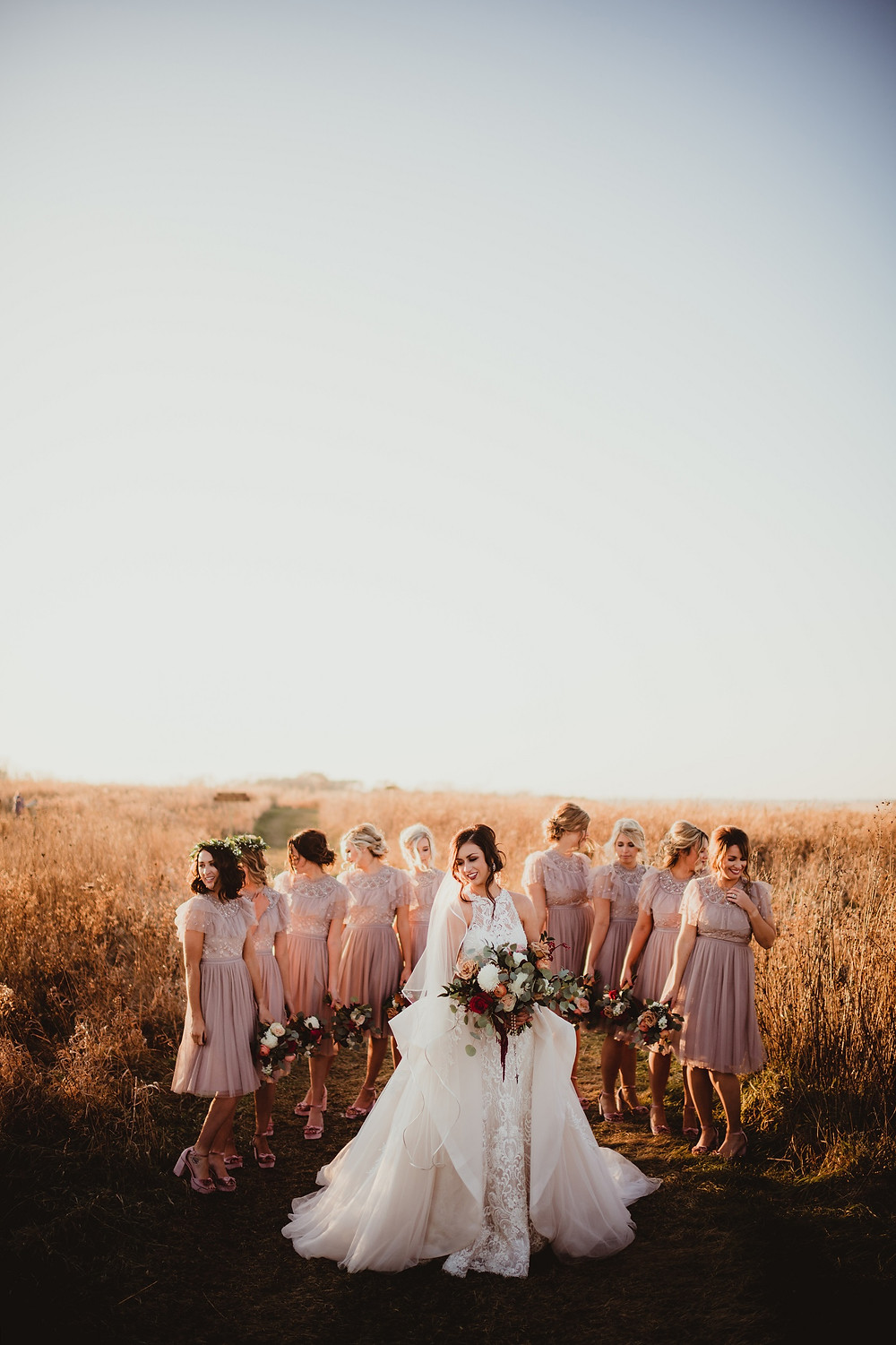 Bride and bridesmaids in an autumn field at sunset with fall bridal and bridesmaid garden bouquets by Studio Bloom Iowa