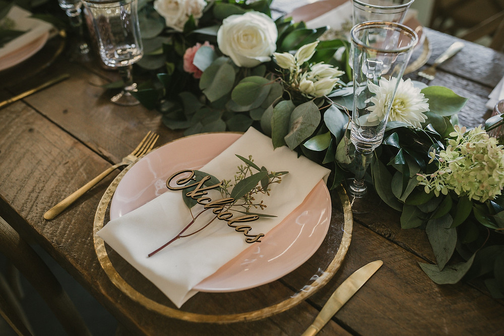 wood place name on blush plate on farm table with accents of gold and eucalyptus garland with flowers by studio bloom iowa