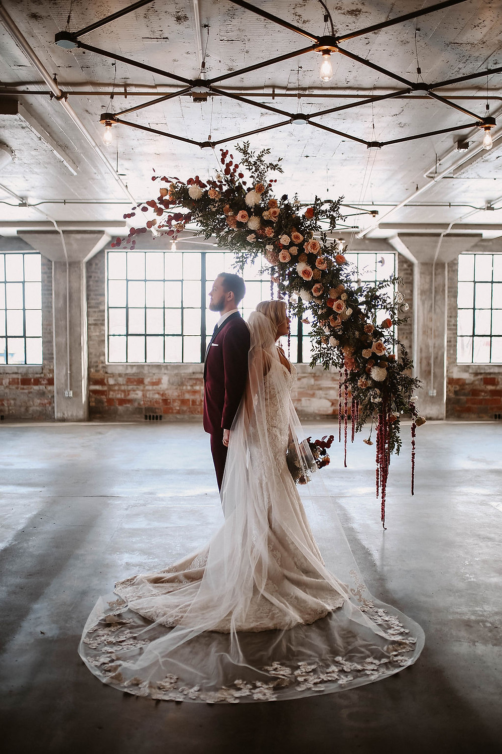 Studio Bloom Iowa hanging floral wedding ceremony installation in peach, burgundy, and white
