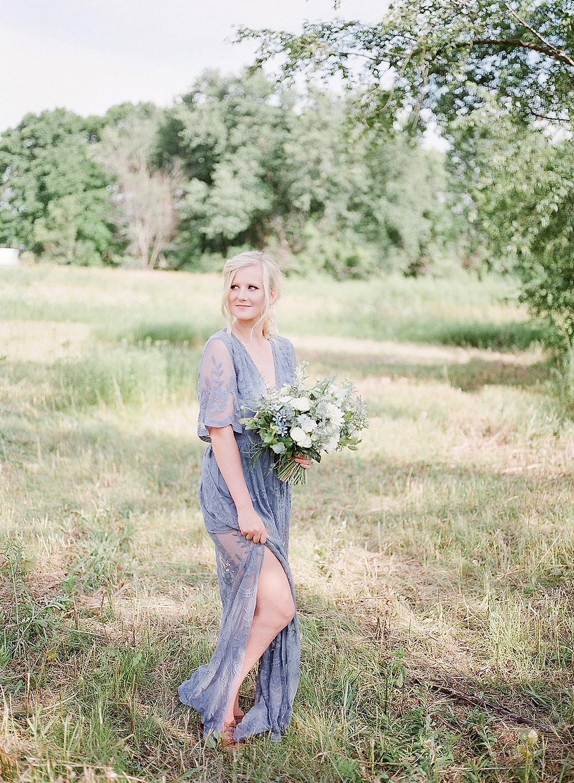 woman in a field wearing a dusty blue dress holding white flower bouquet