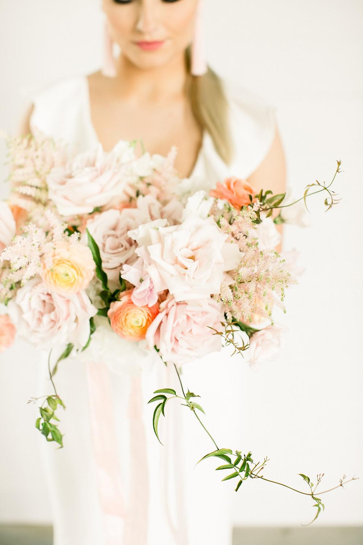 Blush and peach garden bridal bouquet by Studio Bloom Iowa wedding florist of roses, ranunculus, astilbe, and jasmine vine