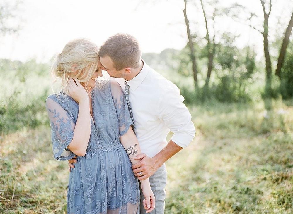 couple snuggling in a prairie