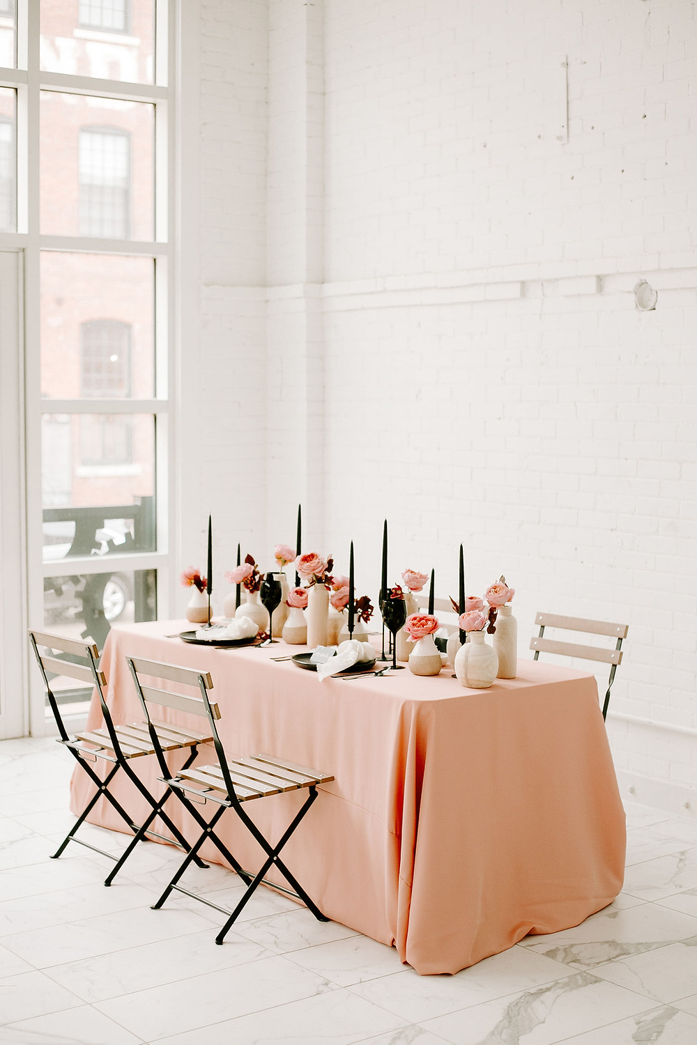 Modern pink and black wedding table setting with garden roses, wood vases, and black accents at the driftless venue