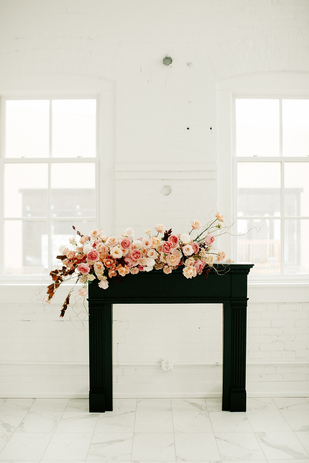 Studio Bloom Iowa wedding florist pink and peach large flower arrangement on black fireplace mantel with roses and carnations