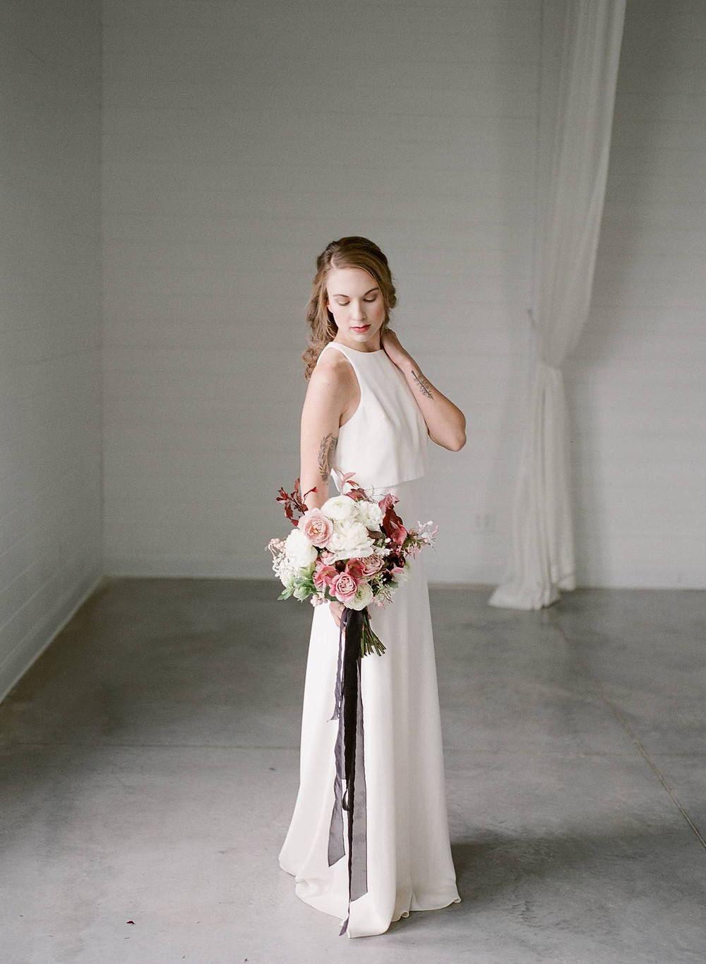 Modern bride with Studio Bloom Iowa flower bouquet of peonies, roses, ranunculus, hellebores, and plum at ashton hill farm