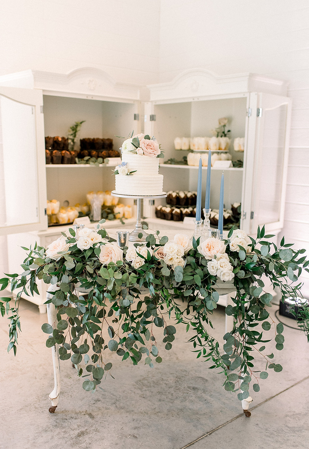 Wedding cake display at Ashton Hill Cedar Rapids with draping greenery and rose arrangement by Studio Bloom Iowa on vanity