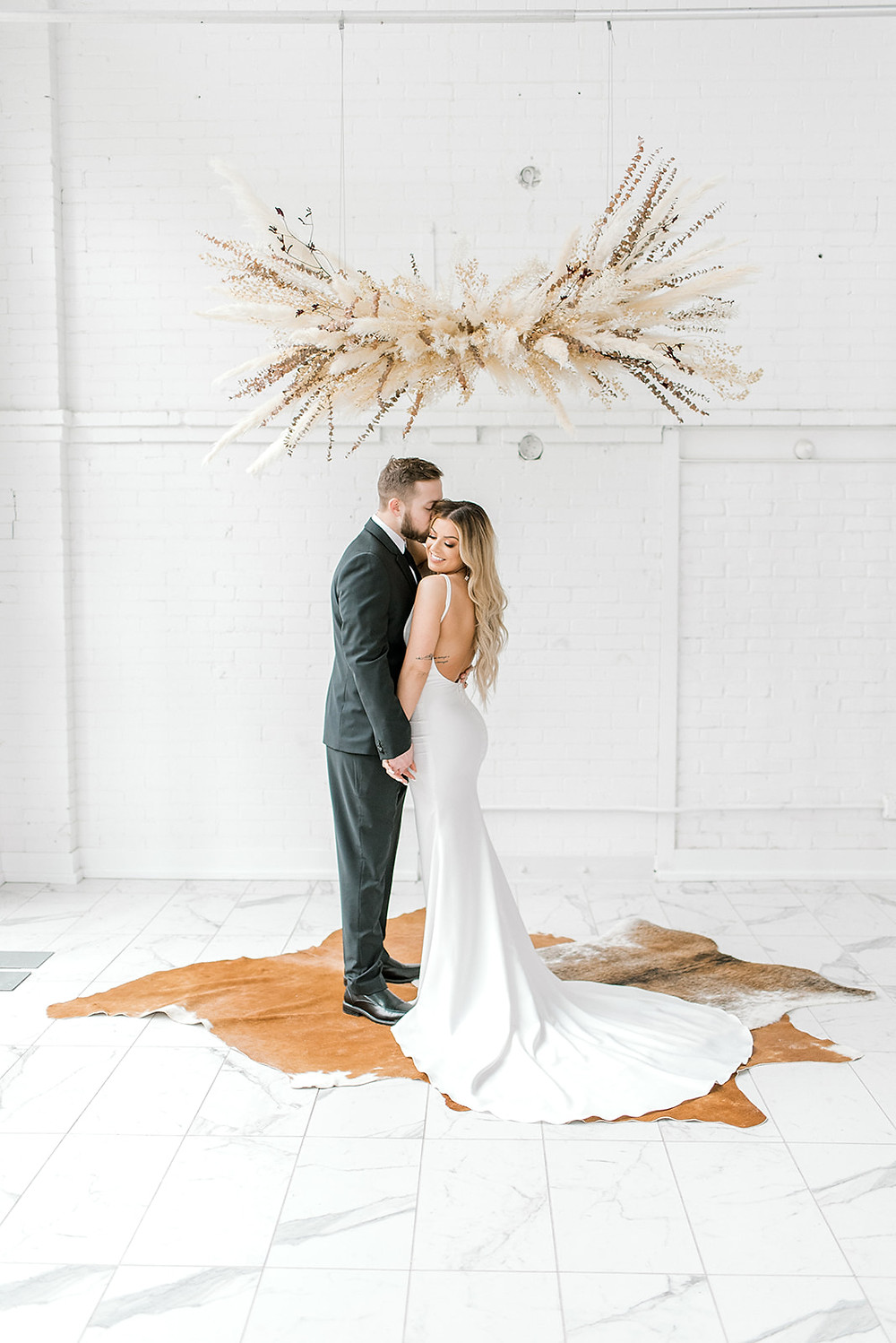 hanging pampas grass ceremony arrangement by Studio Bloom Iowa with modern bride and groom
