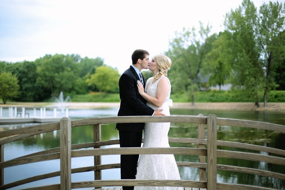 Bride and groom kissing on bridge at pond in New Hampton, Iowa