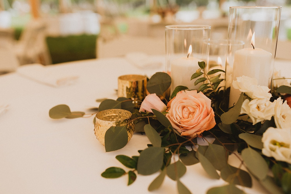 detail of candle centerpiece with greenery and roses
