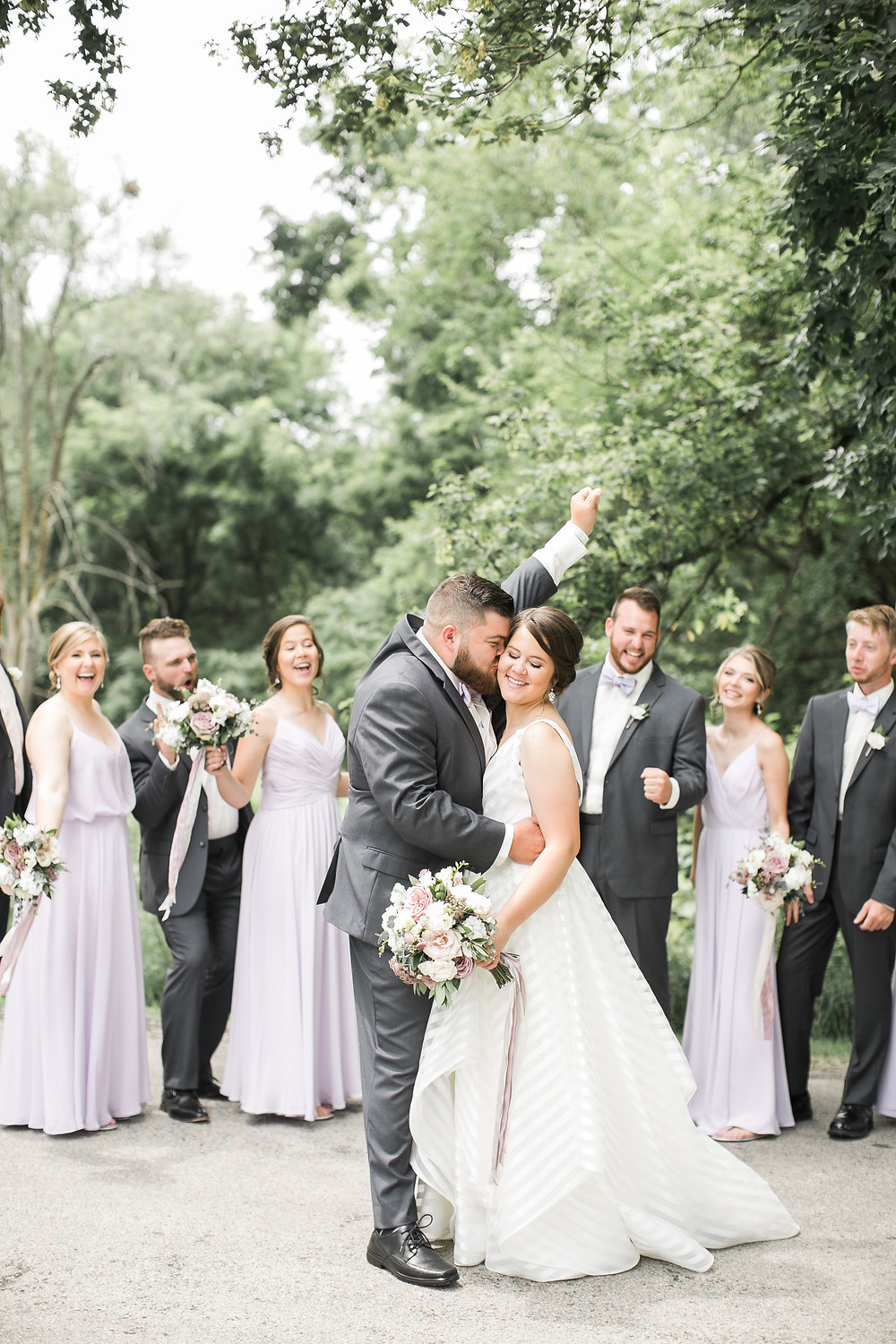 bride in striped wedding dress holding a bridal bouquet and groom cuddling with bridal party looking on and cheering