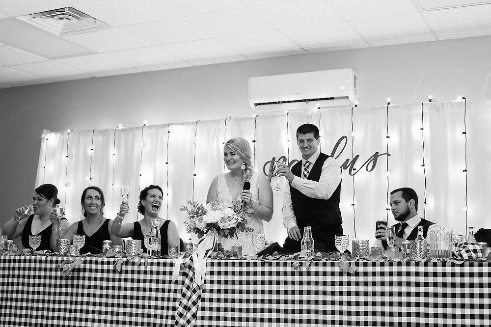 Bridal party toasting at head table with buffalo check tablecloth linens and bistro light backdrop at Waucoma Event Center