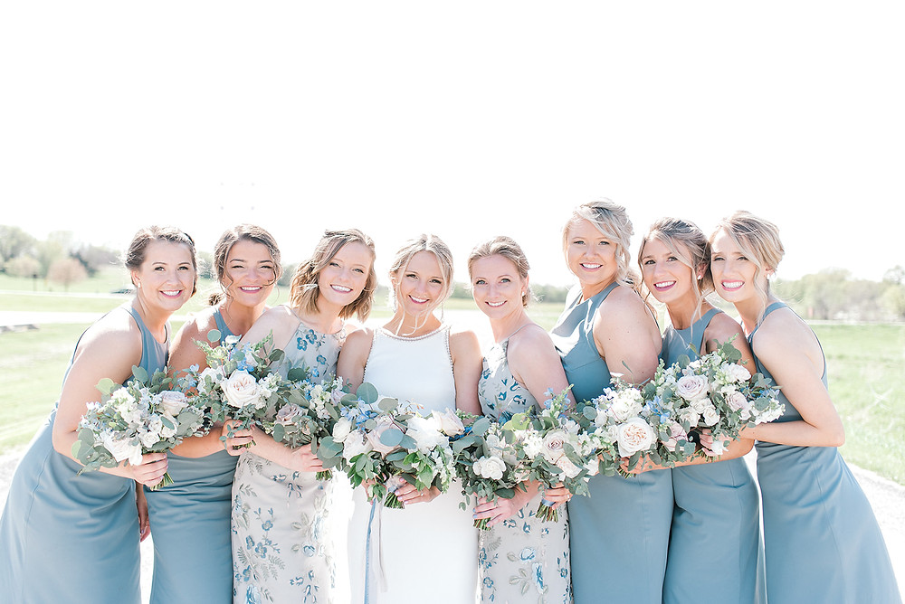 Bride and bridesmaids in slate blue dresses with blush and blue wedding bouquets by Studio Bloom Iowa wedding florist