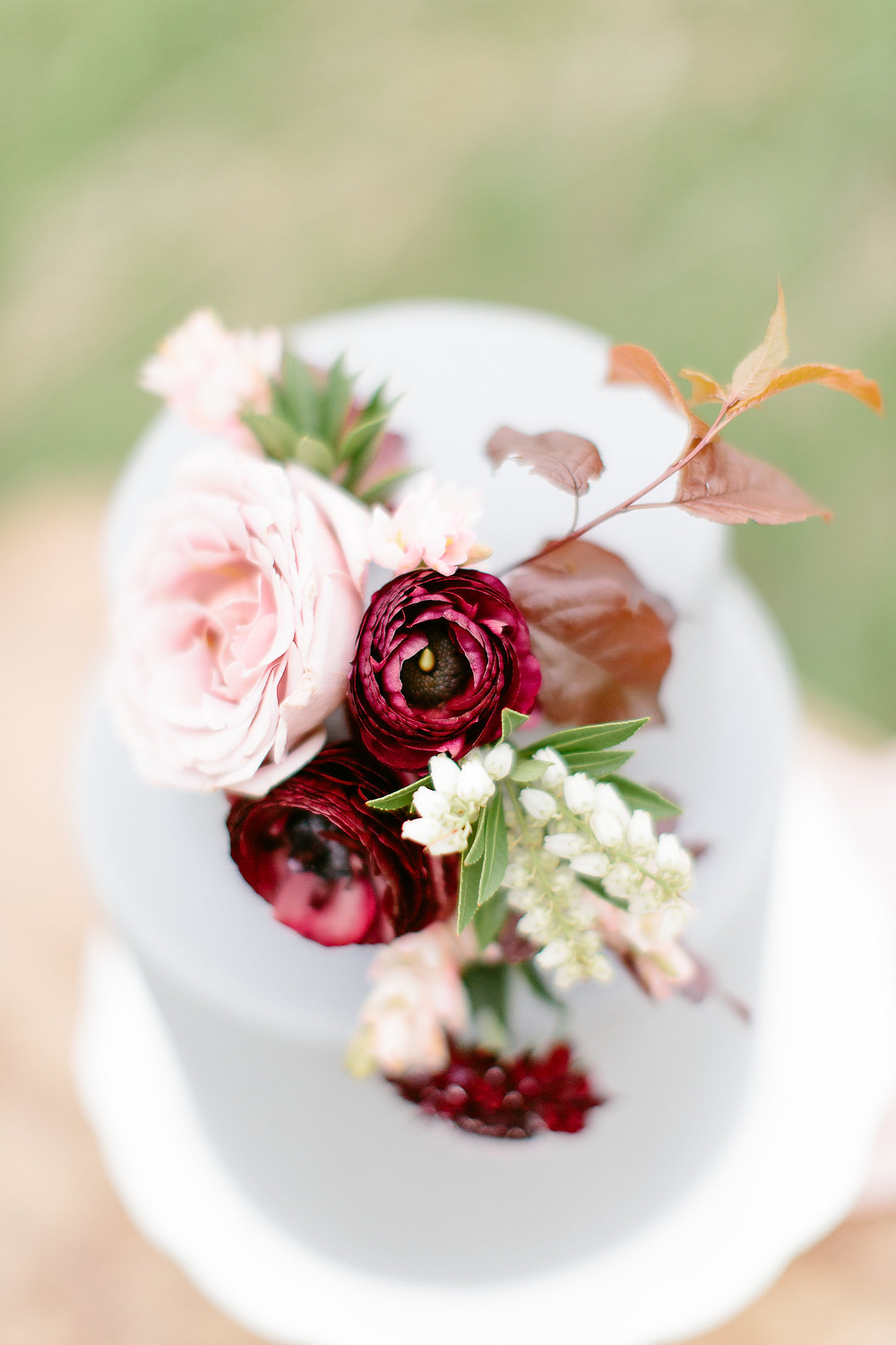 burgundy ranunculus and blush roses with pieris flower cake topper on grey fondant cake