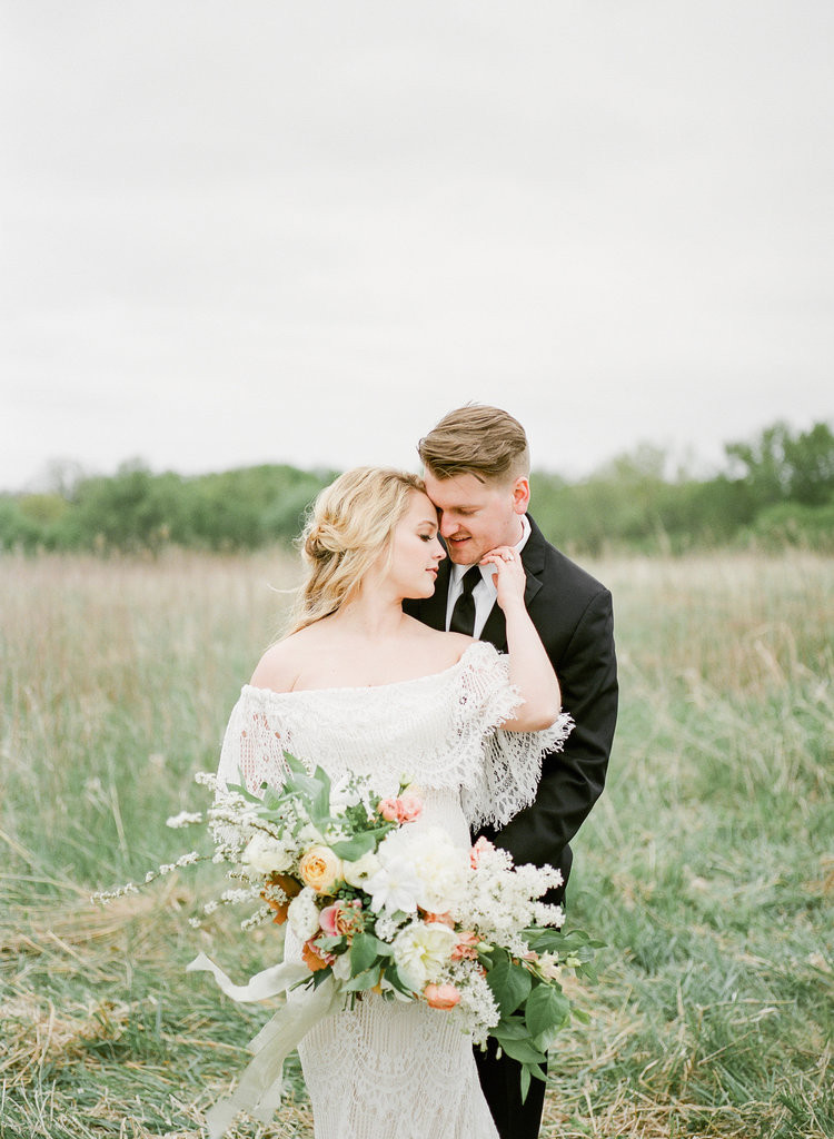 bride and groom in Iowa countryside with bridal bouquet by Studio Bloom wedding florist