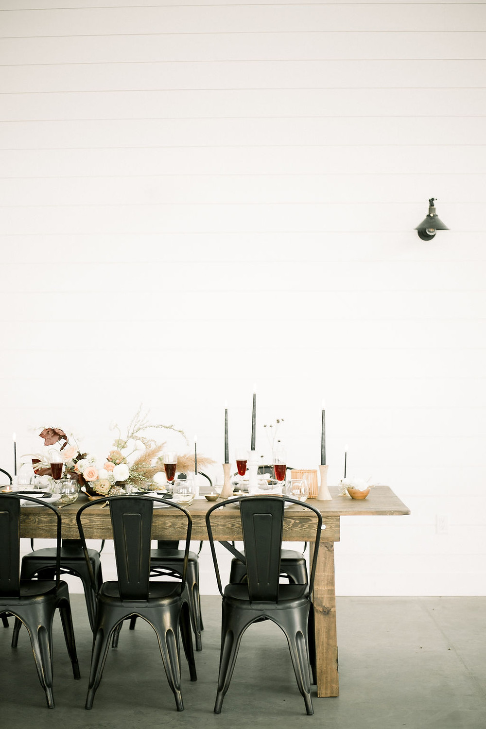 Modern minimalist wedding table with metal chairs at Walker Homestead in Iowa City with black candles and warm wood tones