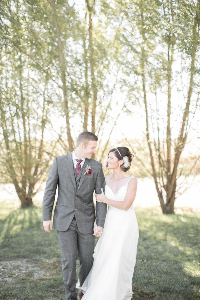bride and groom walking on sutliff cider iowa farm on their wedding day