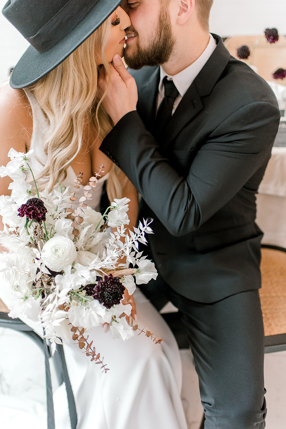 modern bride and groom with bridal bouquet of ranunculus, scabiosa, and bleached ruscus by Studio Bloom Iowa wedding florist