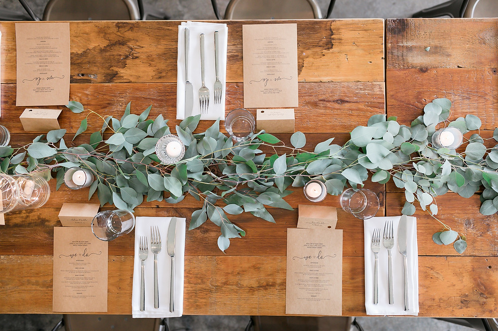 Eucalyptus runner centerpiece on wood farm table with candles and dinner menus at Rapid Creek Cidery by Studio Bloom Iowa