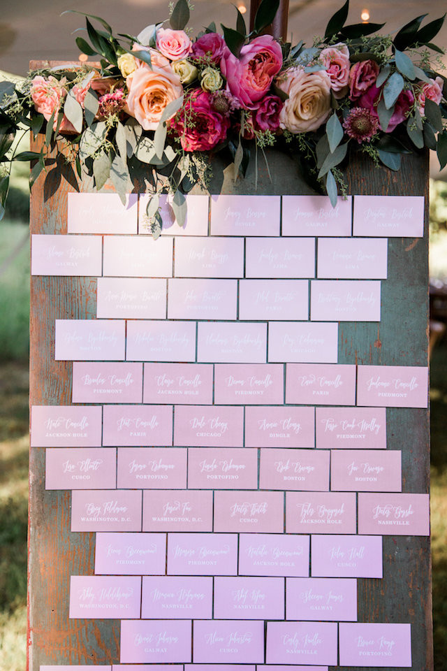 rustic wood escort card display with floral by studio bloom iowa for summer pastel farm wedding with roses in pink and peach
