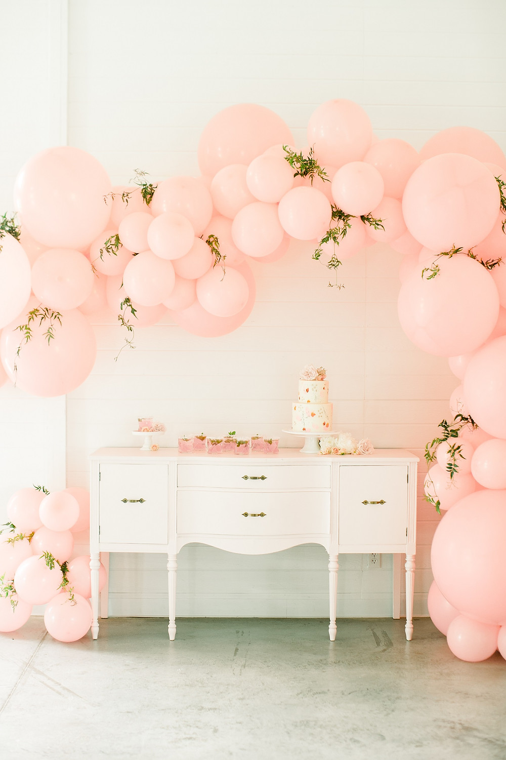 Pink balloon arch with greenery over wedding cake table display on pink vintage buffet at ashton hill farm in cedar rapids