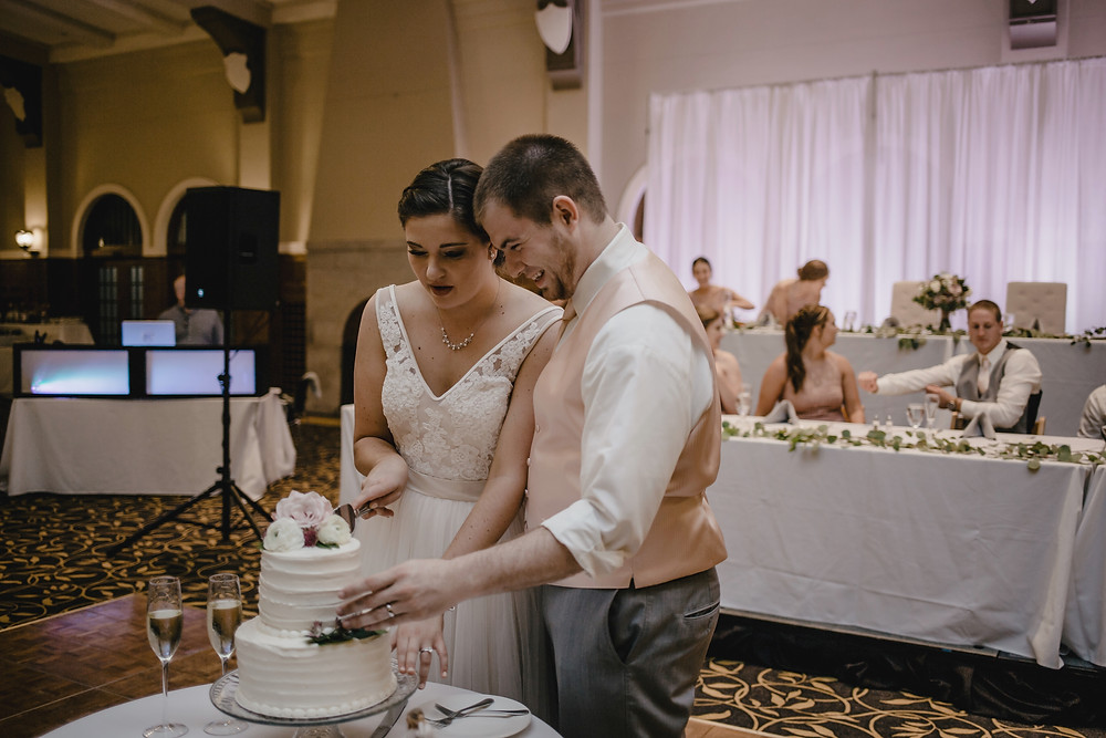 bride and groom cutting white wedding cake at IMU ballroom in Iowa City