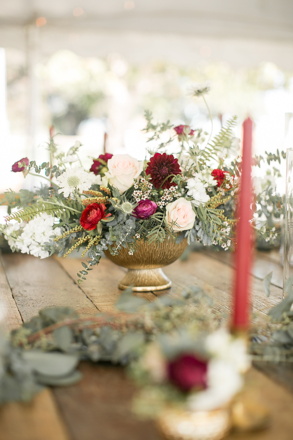 wedding reception flower centerpiece by studio bloom iowa in shades of burgundy and blush in gold compote vase