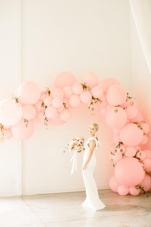 Bride under pink balloon arch holding blush bridal bouquet by Studio Bloom Iowa wedding floral designer at Ashton Hill Farm
