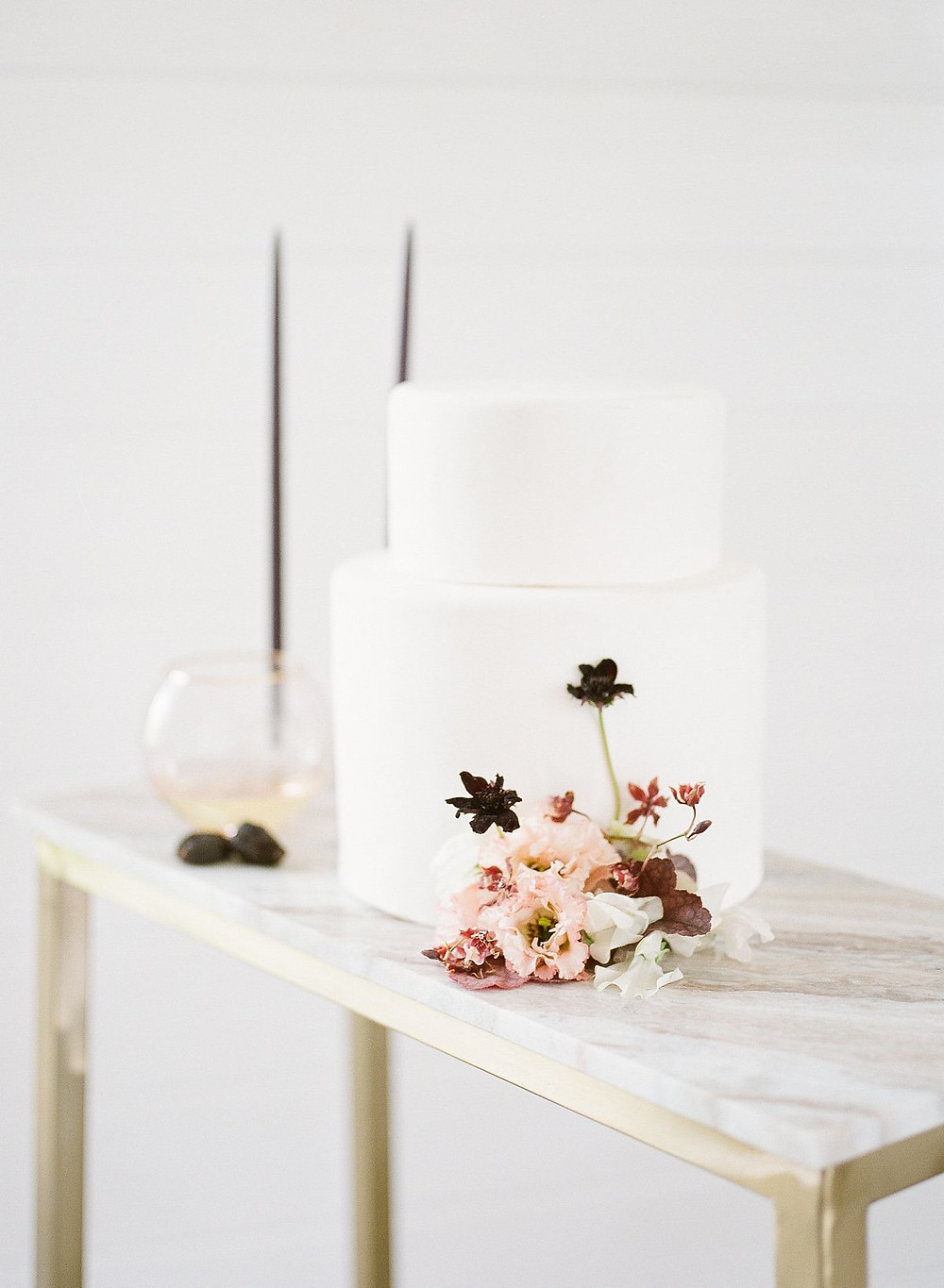 minimalist white fondant wedding cake with peach and burgundy flowers