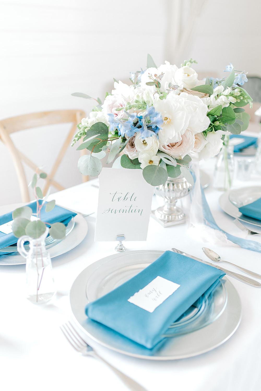 Lush white, blush, and light blue centerpiece in silver urn by Studio Bloom Iowa at Ashton Hill Farm wedding venue