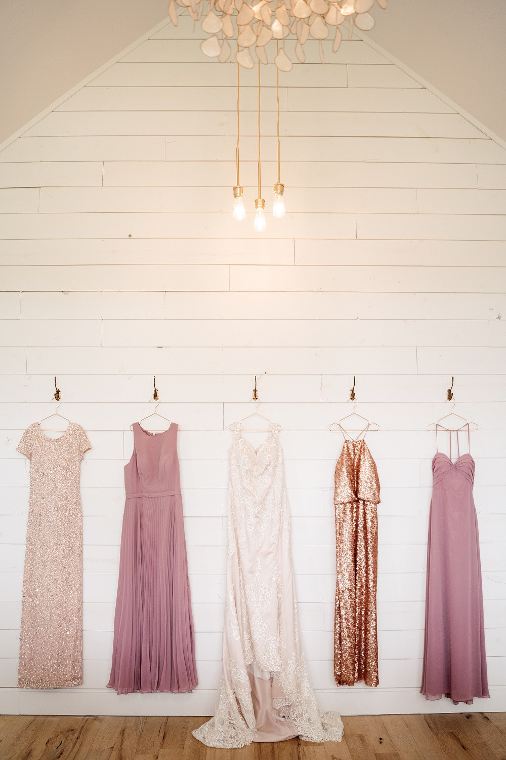 blush and mauve bridesmaid dresses hanging against shiplap wall at Little Lights