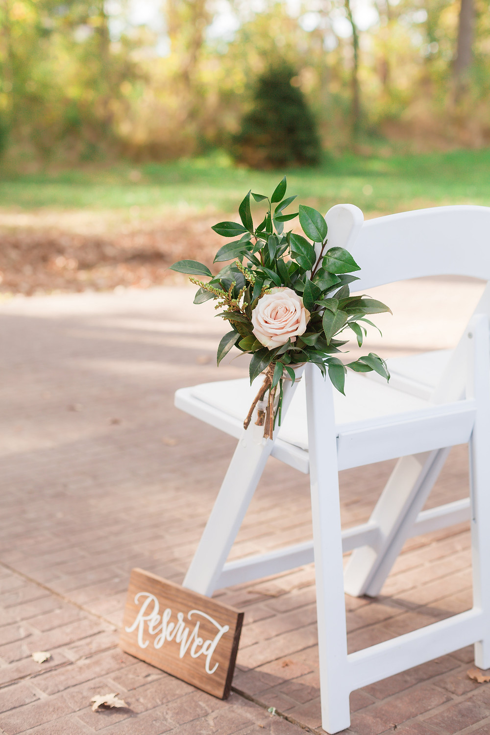 Rose aisle marker with greenery on white chair for outdoor wedding by studio bloom iowa wedding florist at rapid creek cidery