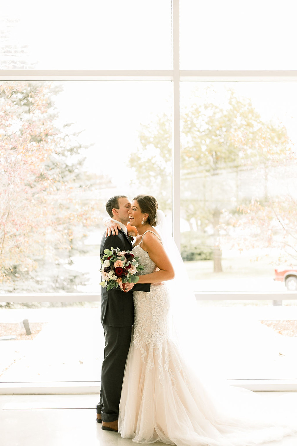 Bride and groom hugging during first look in front of windows holding bridal bouquet in burgundy and white by Studio Bloom Iowa