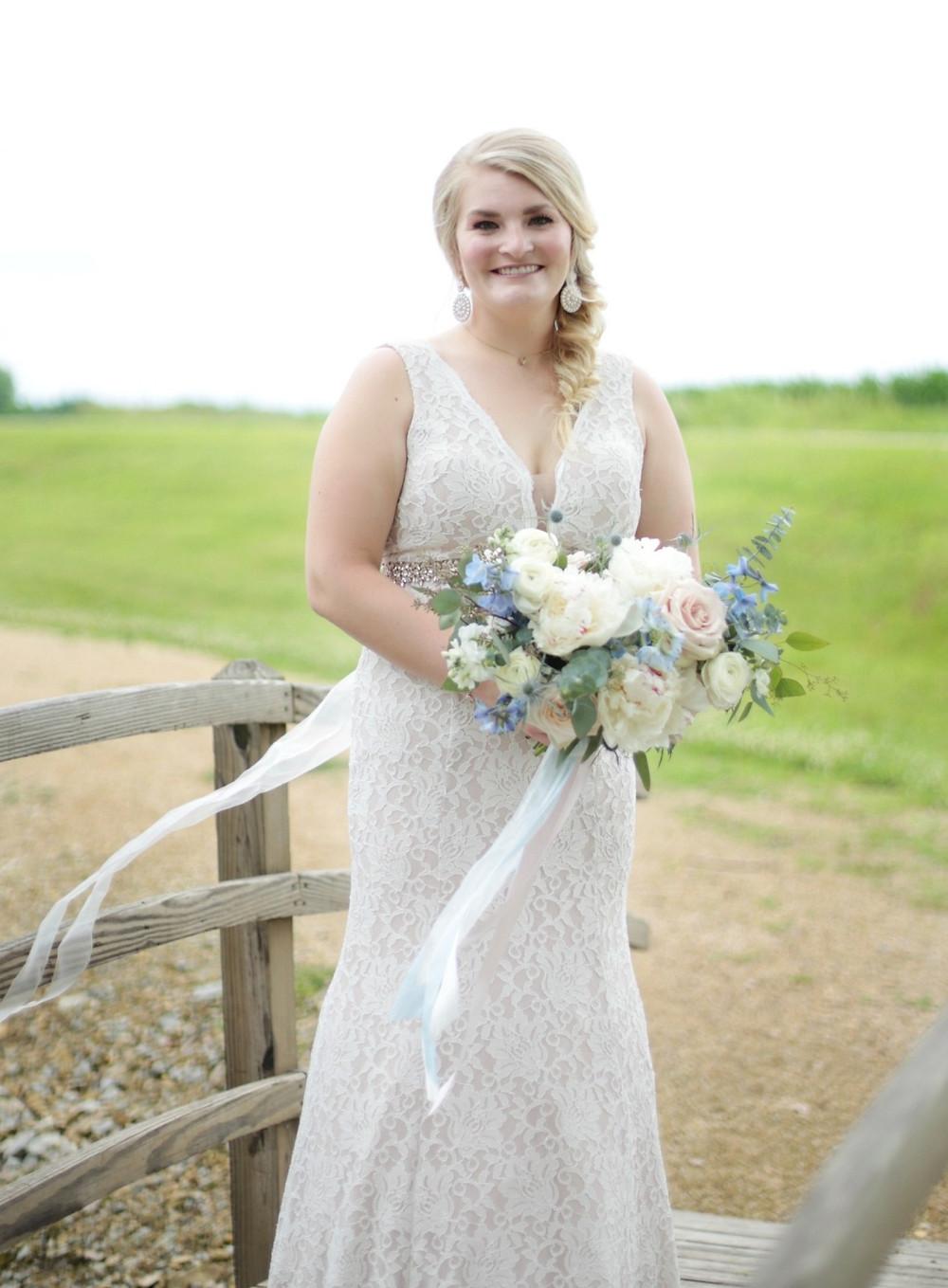 Bride holding Studio Bloom Iowa bridal bouquet in blush and blue with peonies, roses, ranunculus, delphinium, and eucalyptus
