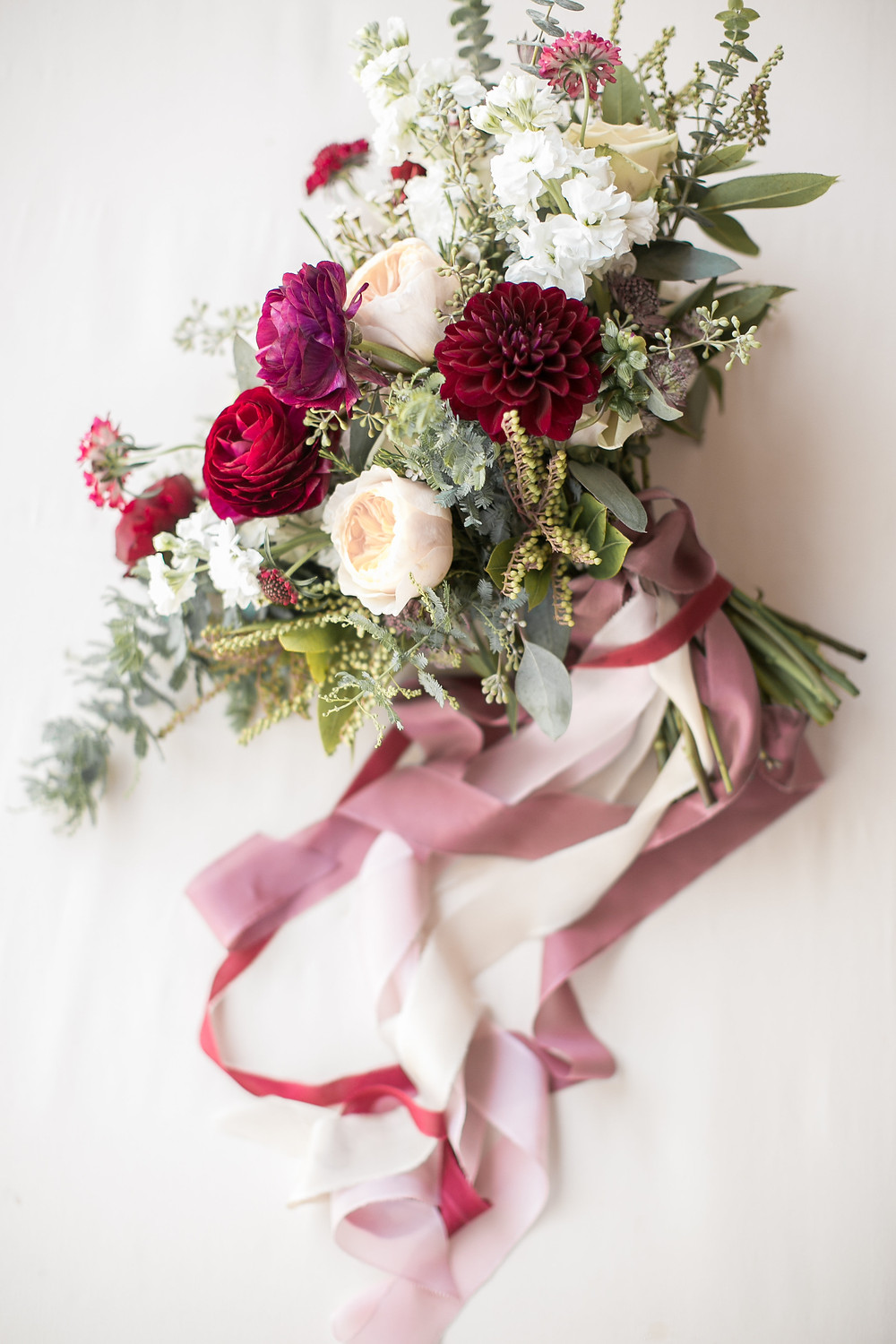 bridal bouquet by studio bloom iowa with dahlias, ranunculus, stock, and eucalyptus in burgundy and blush and trailing ribbon
