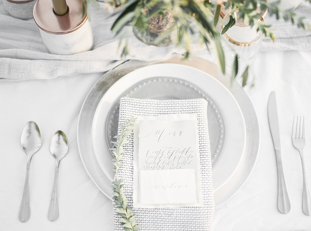 wedding place setting detail with silver charger, plate, and napkin
