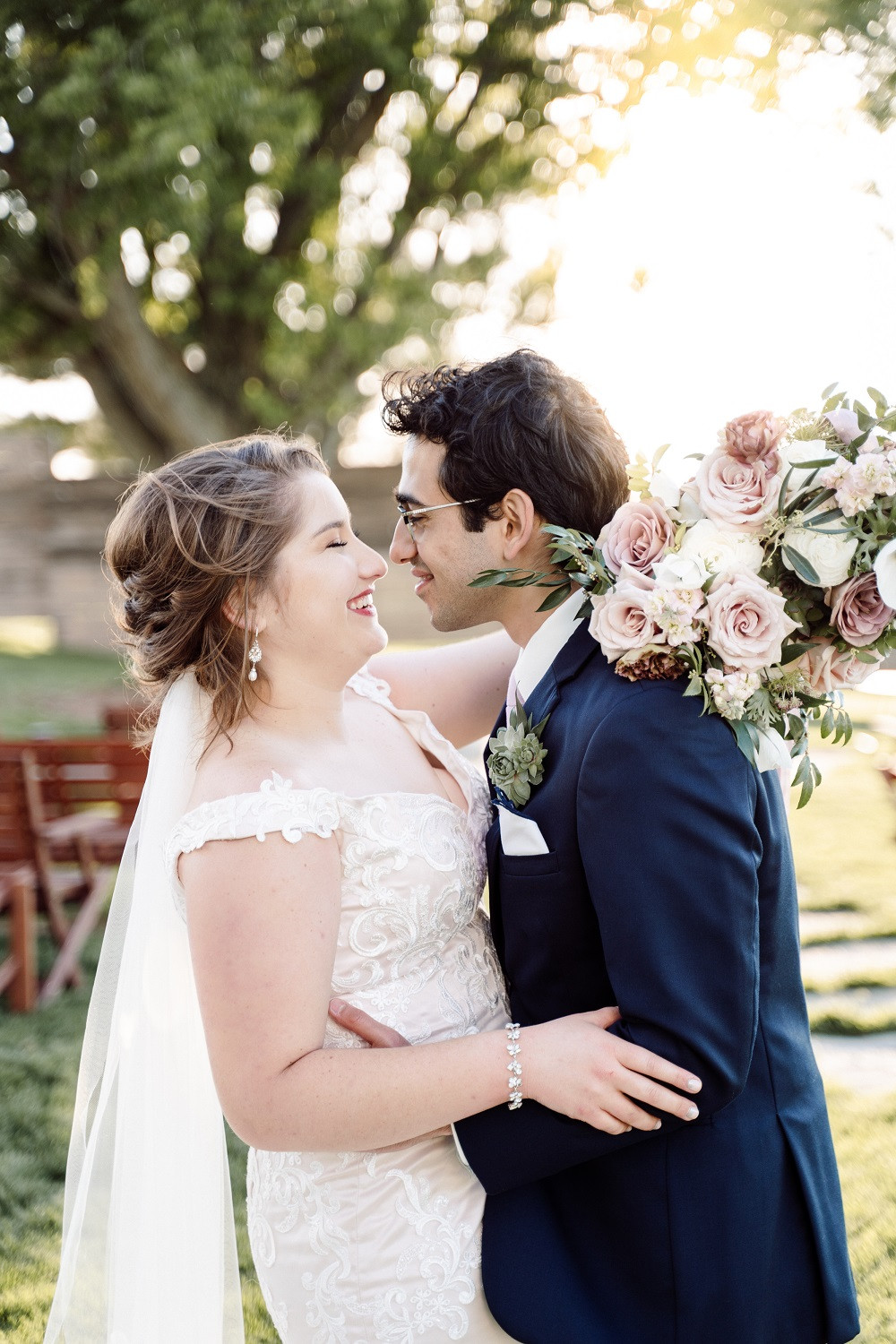smiling bride and groom outside with bridal bouquet by Studio Bloom Iowa