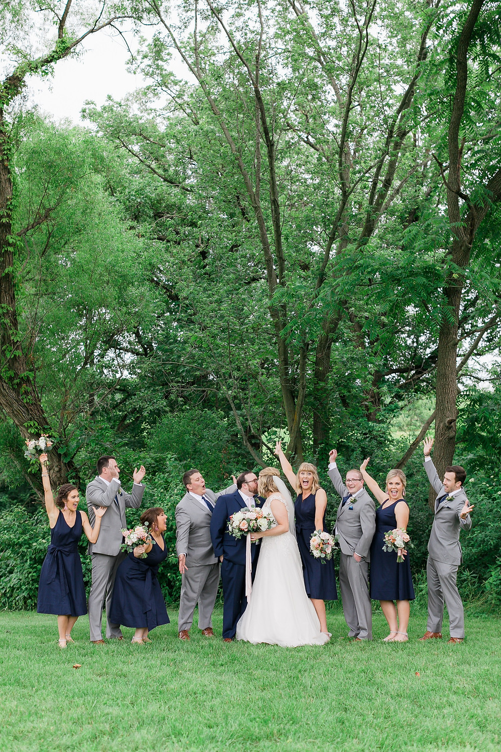 Bridal party cheering in navy bridesmaid dresses and grey suits for outdoor wedding at Rapid Creek Cidery in Iowa City