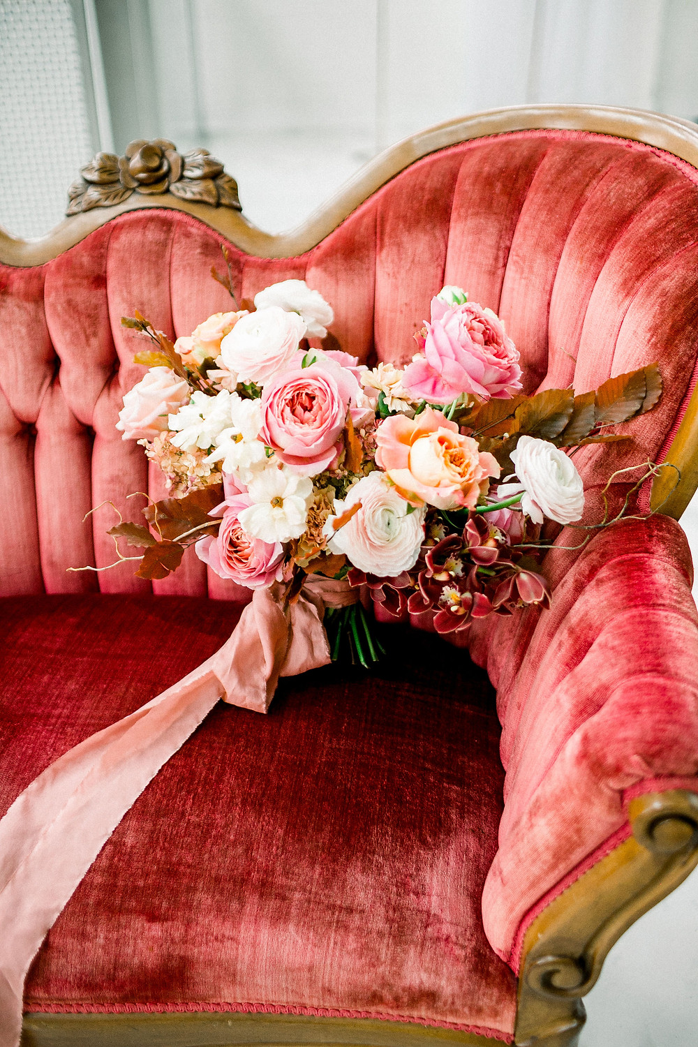 Studio Bloom Iowa bridal bouquet of garden roses, ranunculus, and orchids in pinks and peaches on antique red velvet couch