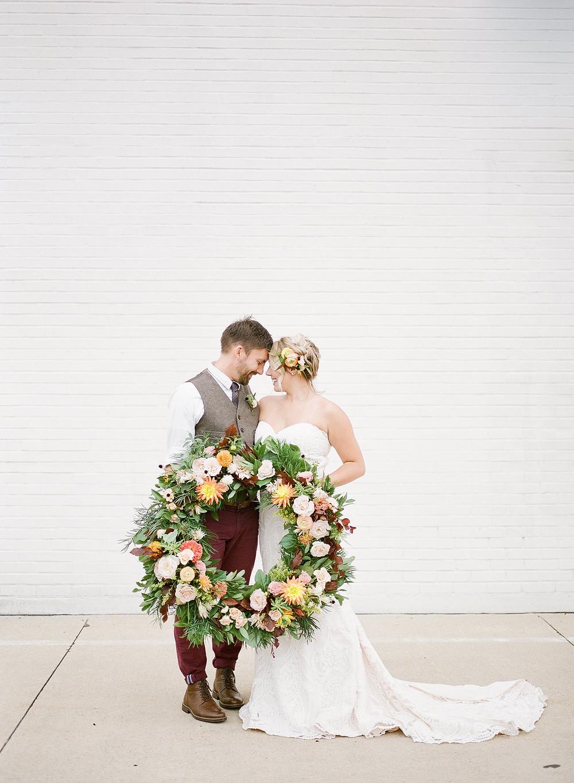 Bride and groom holding large boho floral wreath by cedar rapids wedding florist studio bloom iowa