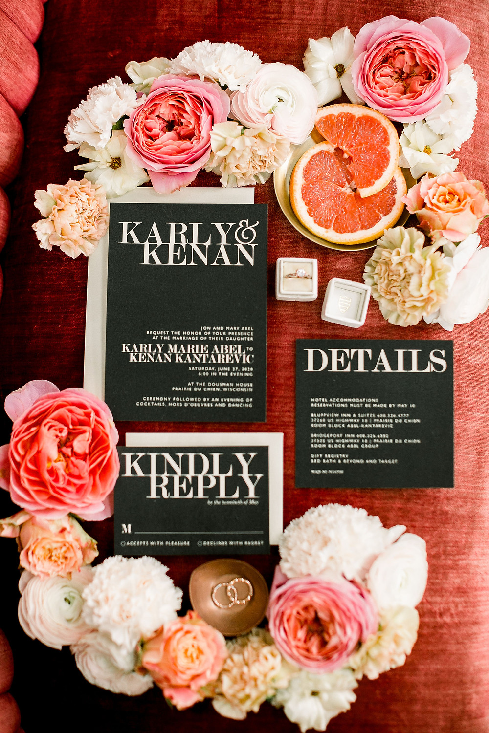 black wedding invitation suite with white lettering surrounded pink and peach flowers on velvet