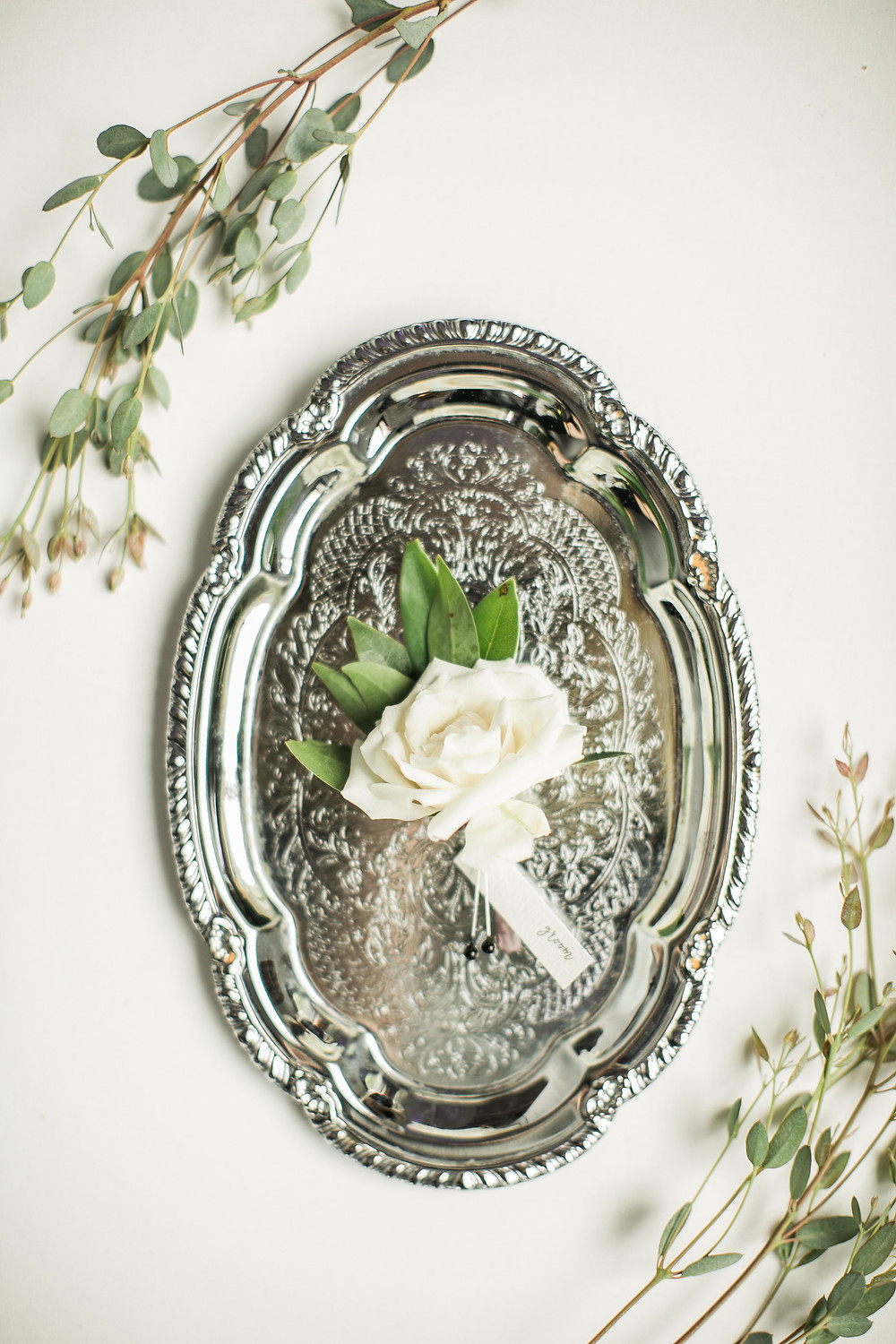 ivory spray rose boutonniere on silver tray