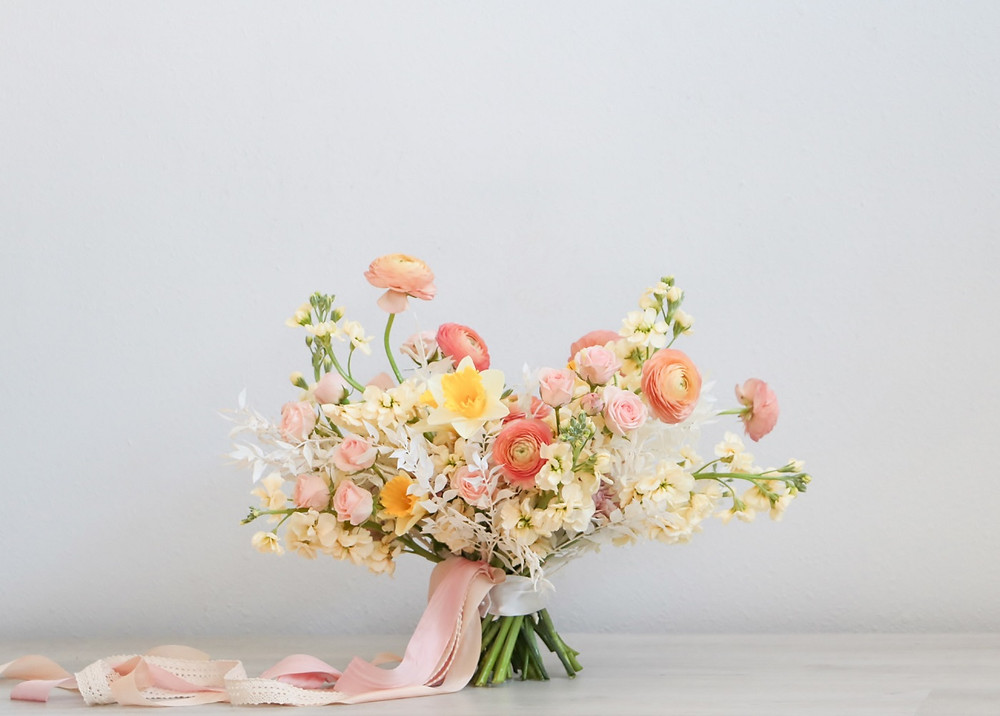 spring bridal bouquet  by Studio Bloom Iowa of daffodils, spray roses, ranunculus, and stock