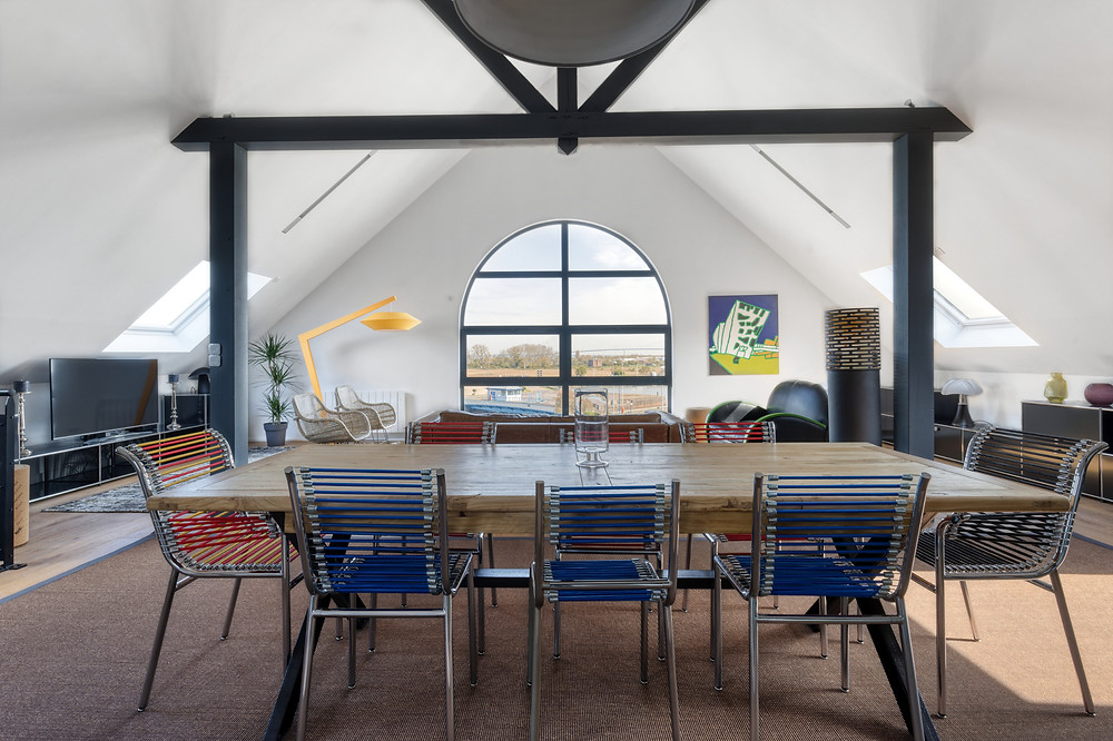 A bright loft apartment with a huge window and ceiling, situated in Honfleur, France.