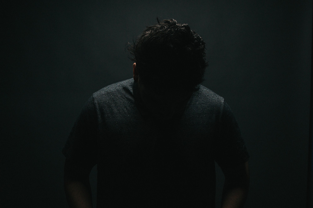 Man in dark shirt stands with head down, in front of a dark background.  You cannot see his face.