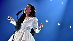 Demi Lovato - a woman wearing a white dress sings with lots of emotion into a microphone, standing in front of a blue background.