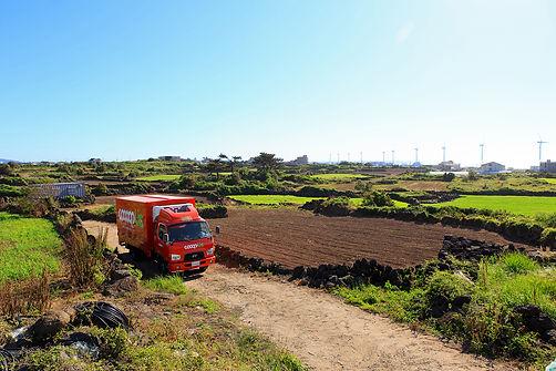 제주희망협동조합 쿱어스 물류트럭이 제주도의 시골 마을에서 물건을 싣고 있습니다.